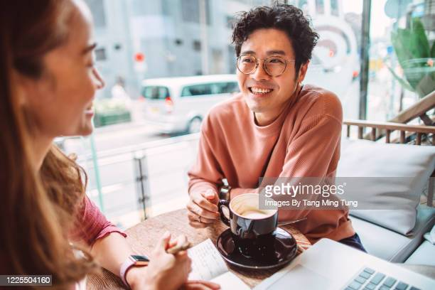 business partners working joyfully together on laptop computer in cafe - trust stock pictures, royalty-free photos & images