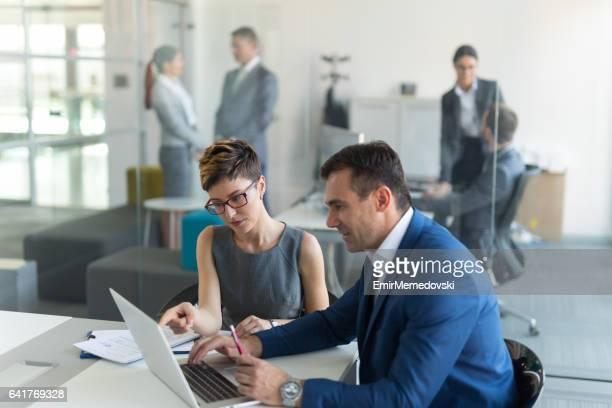 Business people analyzing market research data using laptop