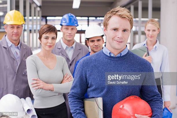 Business people and construction workers posing