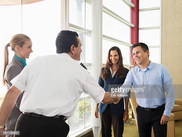 Business people and pilot shaking hands