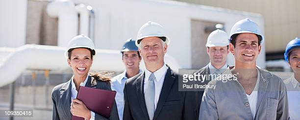 Business people and worker in hard-hats standing outdoors