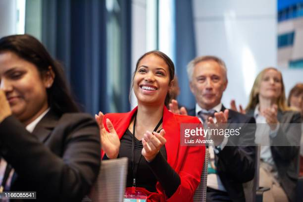 business people applauding during launch event - bijwonen stockfoto's en -beelden
