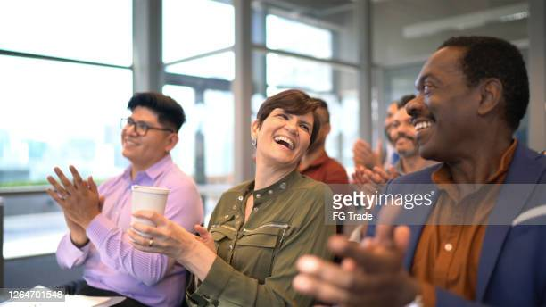 business people applauding their colleague after seminar in board room - applauding stock pictures, royalty-free photos & images