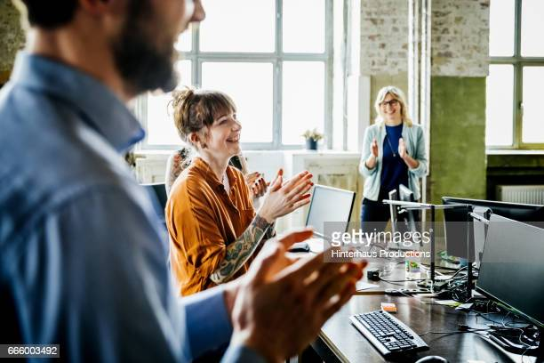 Business people applauding to colleague in office