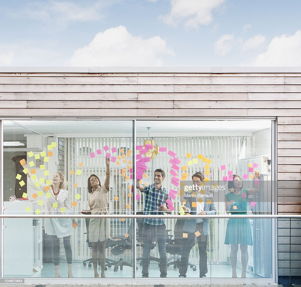 Business people applying adhesive notes to window : Stock Photo