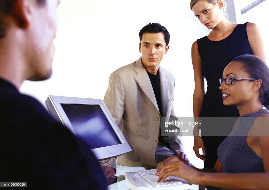 Business people around computer : Stockfoto