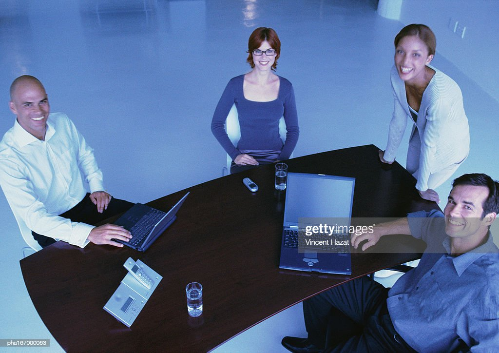 Business people around desk, smiling, elevated view : Stockfoto