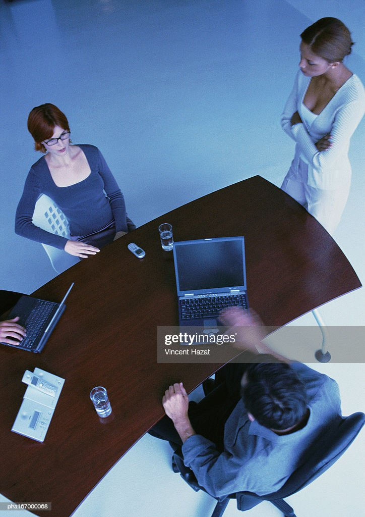 Business people around desk, two with laptops, elevated view : Stockfoto