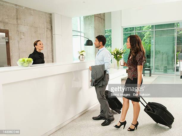 Business people arriving at hotel reception area