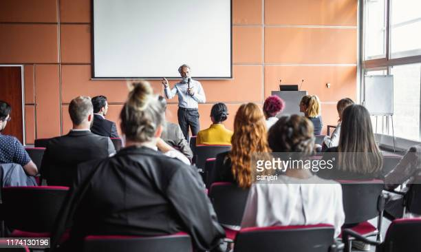 business people at a conference listening to the presenter - staff meeting stock pictures, royalty-free photos & images