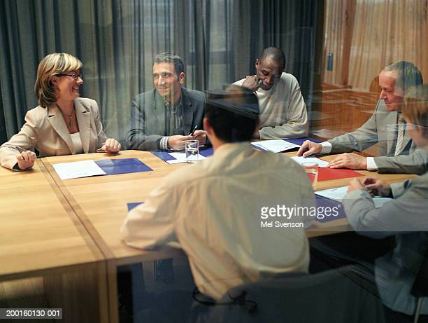 Business people at conference table, view through window