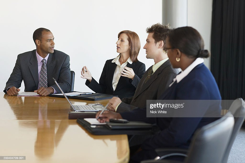 Business people at conference table, woman making hand gestures : Stock Photo