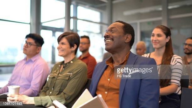 business people attending a conference in a convention center - attending stock pictures, royalty-free photos & images