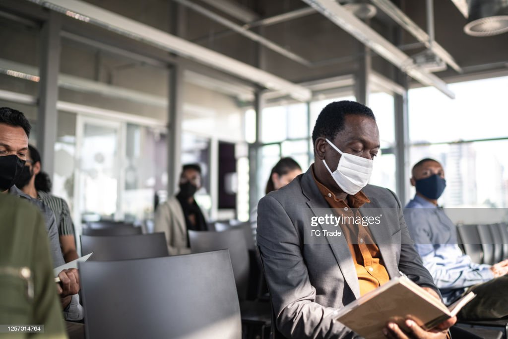 Business people attending a seminar with social distancing and face mask : Stock Photo