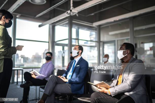 business people attending a seminar with social distancing and face mask - participant stock pictures, royalty-free photos & images