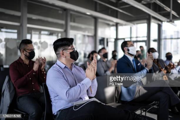 affärsmän som deltar i ett seminarium med socialt avståndstagande och ansiktsmask - opening event bildbanksfoton och bilder
