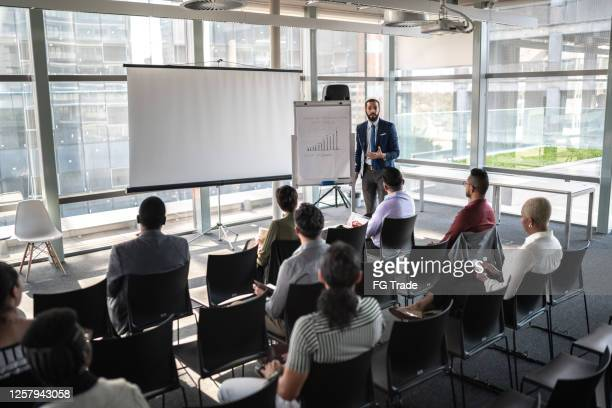 business people attending a seminar with social distancing - press conference stock pictures, royalty-free photos & images