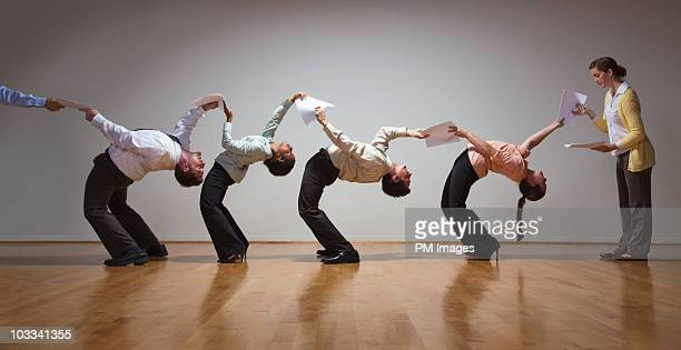 Business people bending over backwards