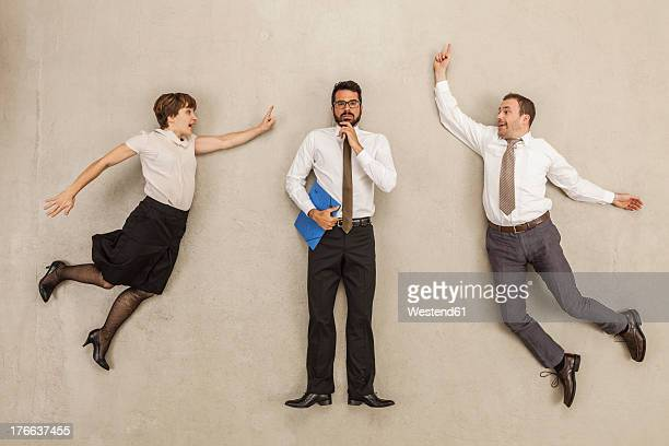 Business people blaming businessman in office