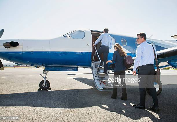 Business people boarding airplane on runway