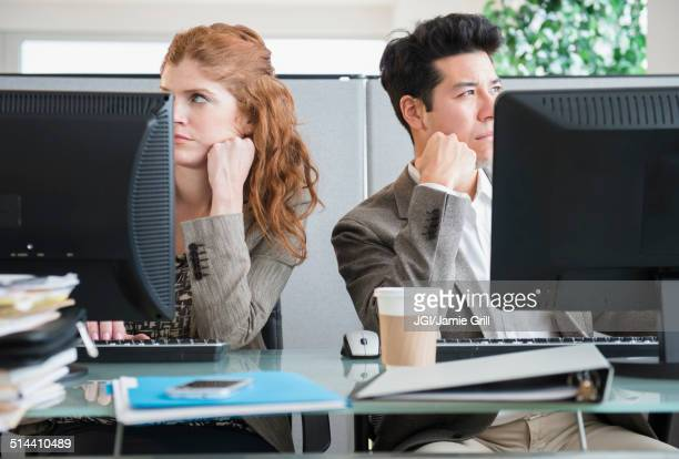 Business people bored at desks