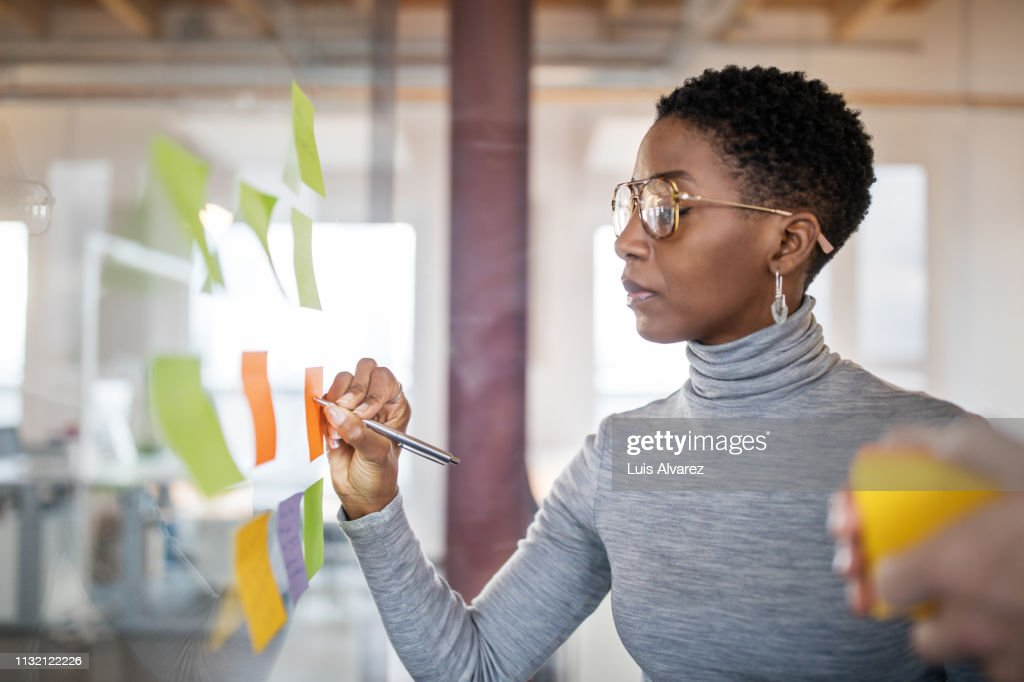 Business people brainstorming using sticky notes : Stock Photo