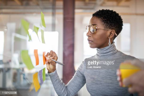 business people brainstorming using sticky notes - brainstormen stockfoto's en -beelden