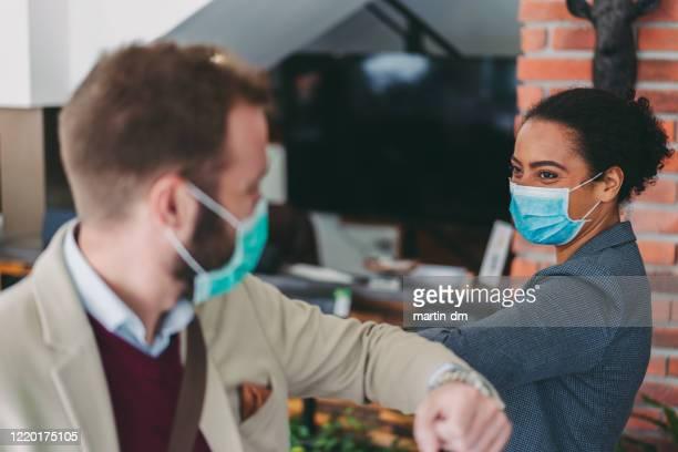 les gens d'affaires bosse coudes comme salutation pendant la pandémie de covid-19 - éviter de se serrer la main photos et images de collection