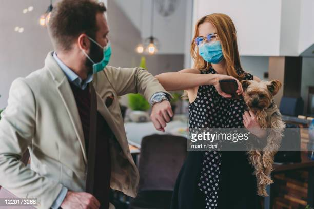 business people bump elbows in office for greeting during covid-19 pandemic - alternative lifestyle stock pictures, royalty-free photos & images