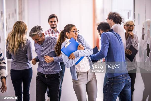 Business people bumping into each other while running in a hallway.