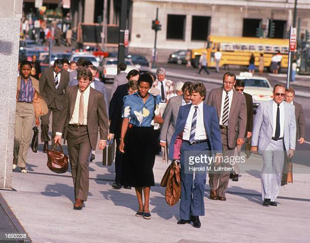 Business people carry briefcases while walking on a city street 1980s