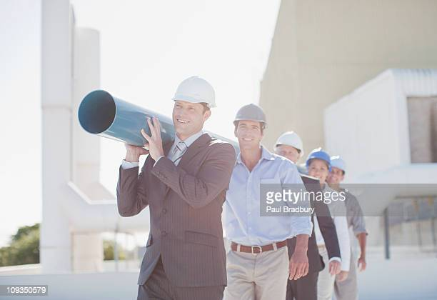Business people carrying large pipe together outdoors