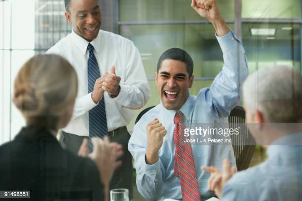 Business people celebrating in office