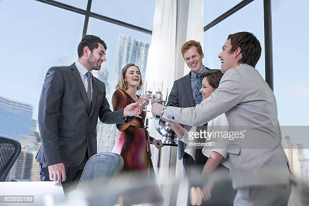 Business people celebrating success in office, clinking glasses