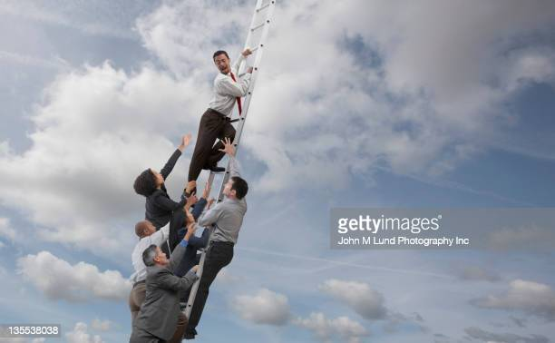 Business people chasing co-worker up ladder into clouds