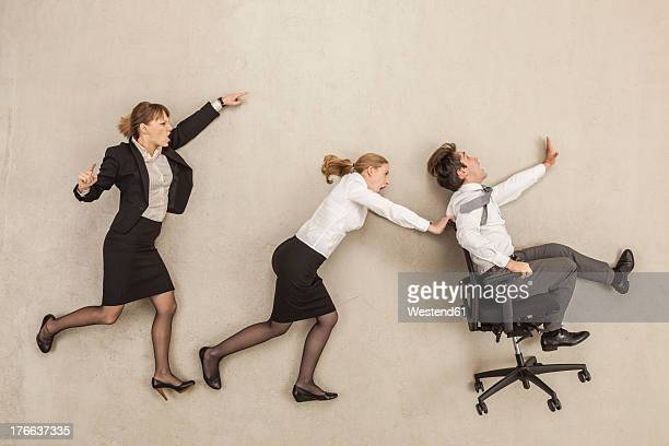 business people chasing in office - 横向きに寝る ストックフォトと画像