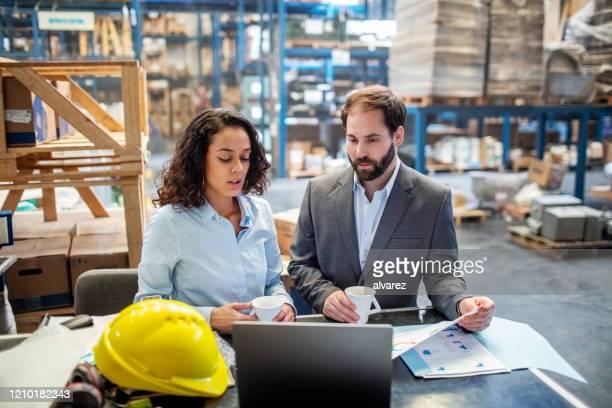 bedrijfsmensen die lijst en inventaris op laptop bij pakhuis controleren - entrepreneur stockfoto's en -beelden