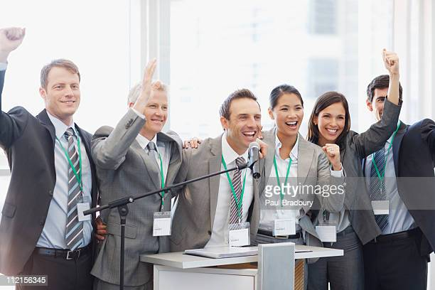 Business people cheering at podium