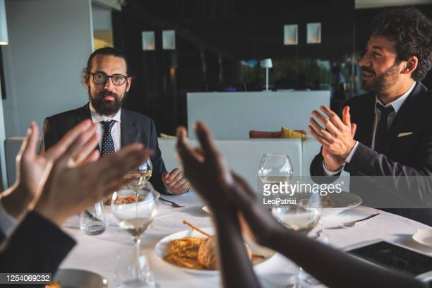 business people clapping for success dining in a luxury restaurant - abbigliamento elegante foto e immagini stock
