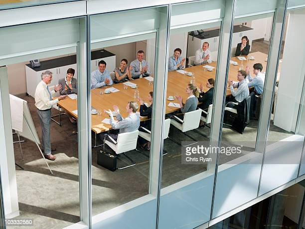Business people clapping in meeting in conference room