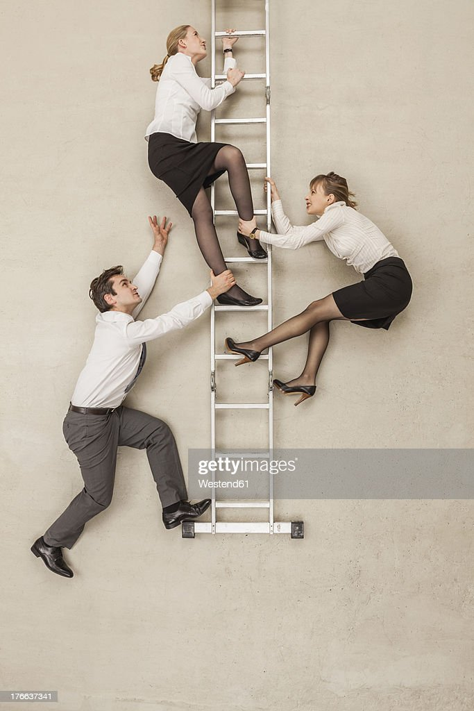 Business people climbing ladder in office : Stock Photo
