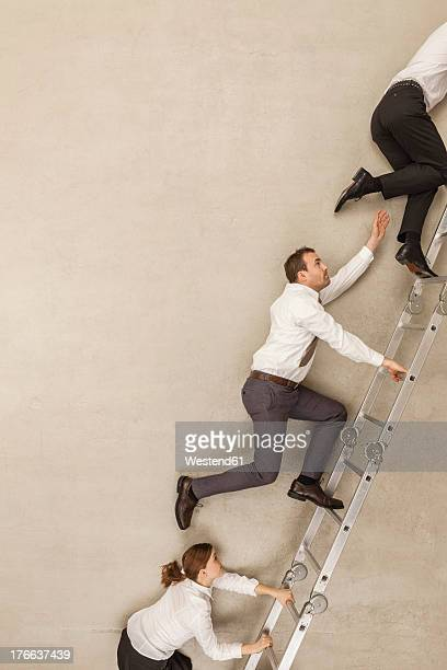 Business people climbing ladder in office