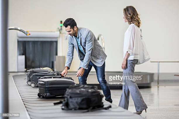 business people collecting their luggage - baggage claim stock photos and pictures