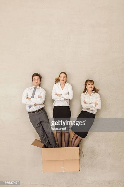 Business people coming out of cardboard box