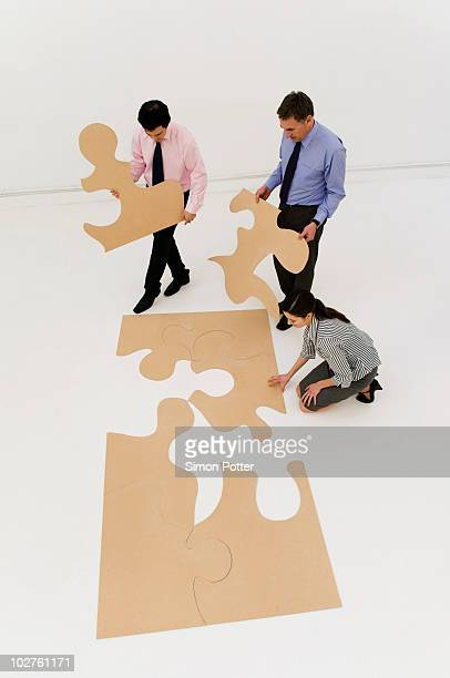 3 business people complete the puzzle