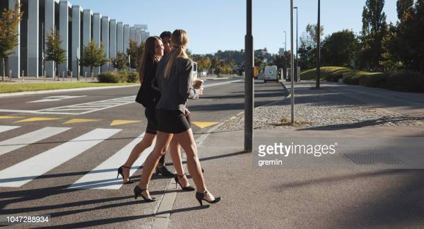 business people crossing the city street - mini skirt stock pictures, royalty-free photos & images