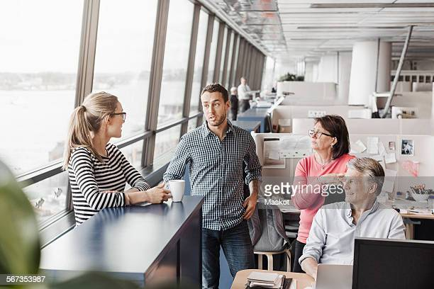 Business people discussing at cubicle in office