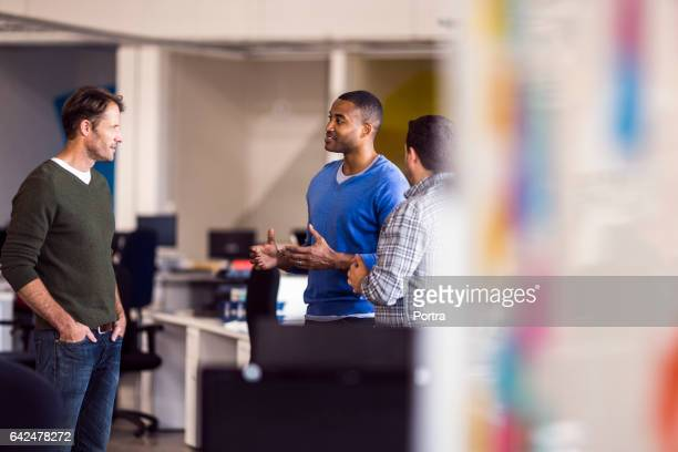 business people discussing at desk in office - hands in pockets stock photos and pictures