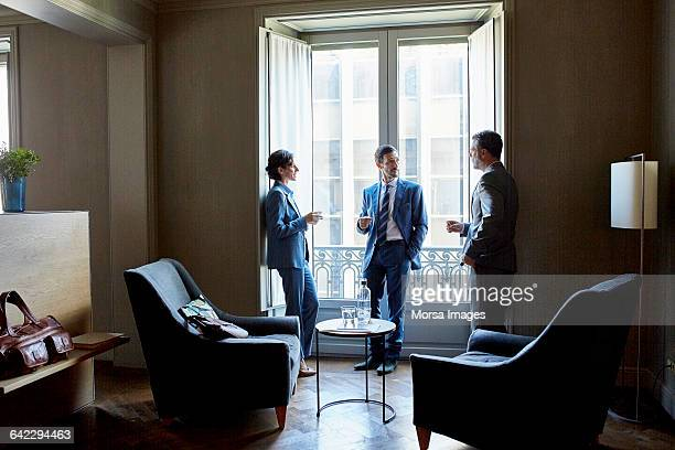 Business people discussing at window in hotel room