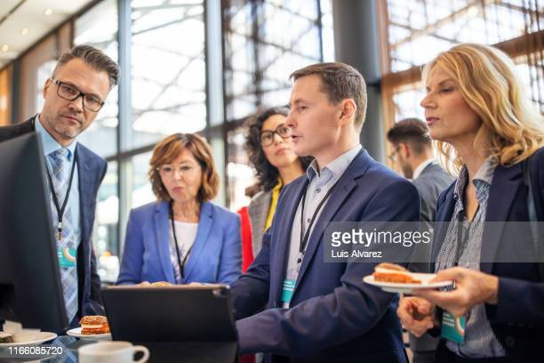 business people discussing during a break in launch event - launch event stock pictures, royalty-free photos & images